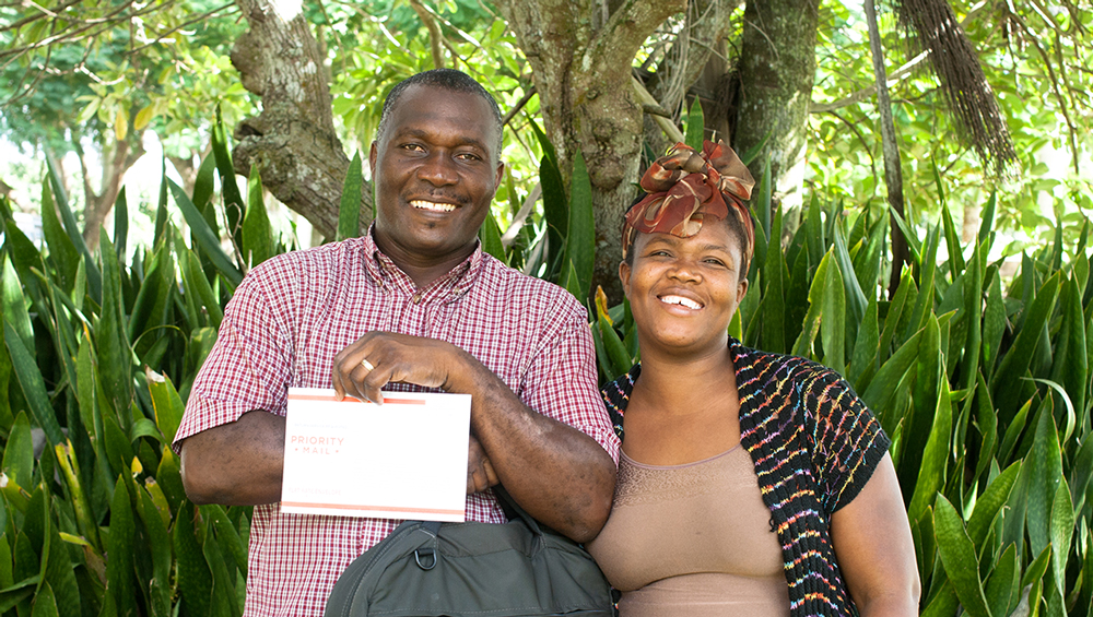 Haitian couple smiling and holding paper