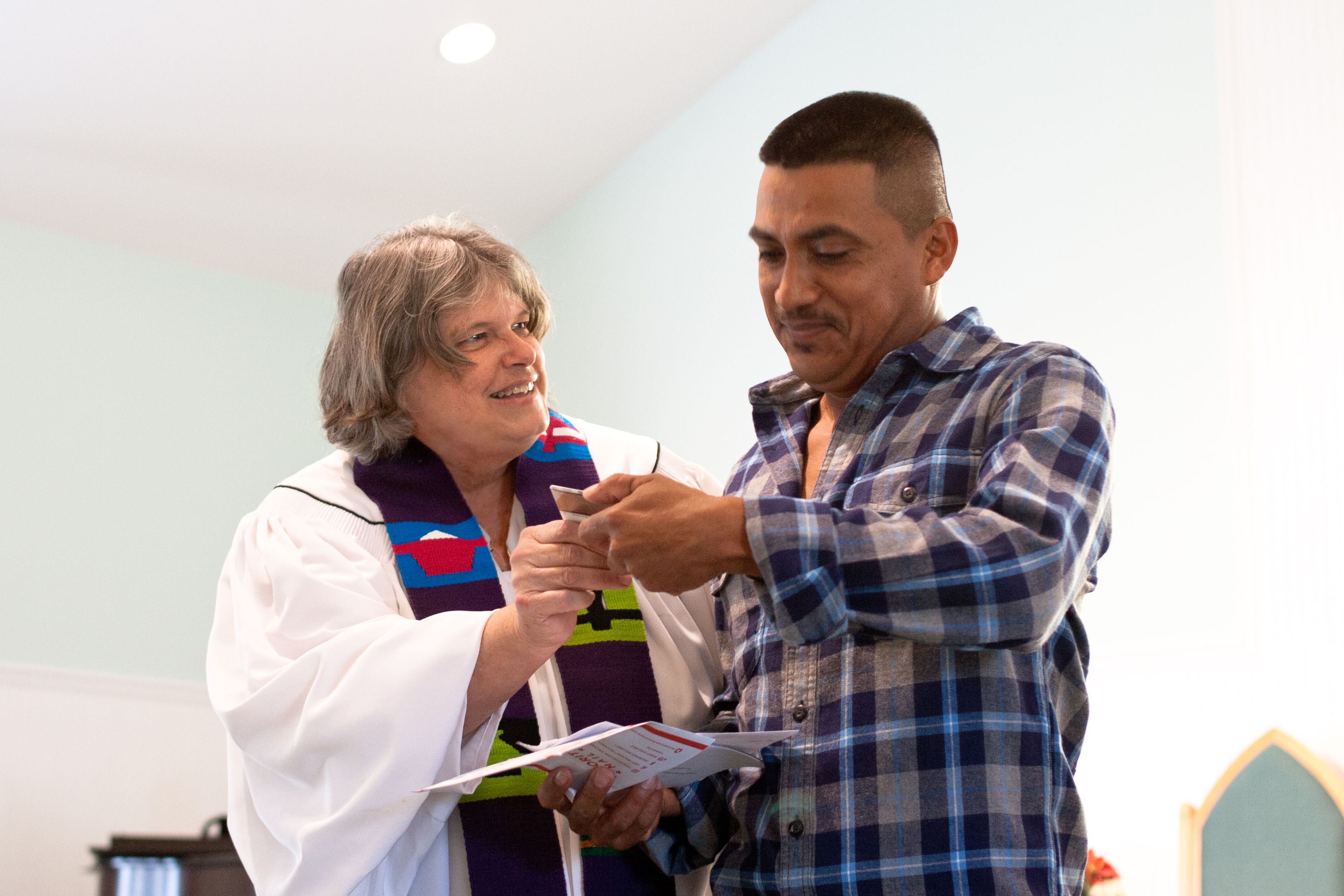 Janet presenting a client with his new Green Card.