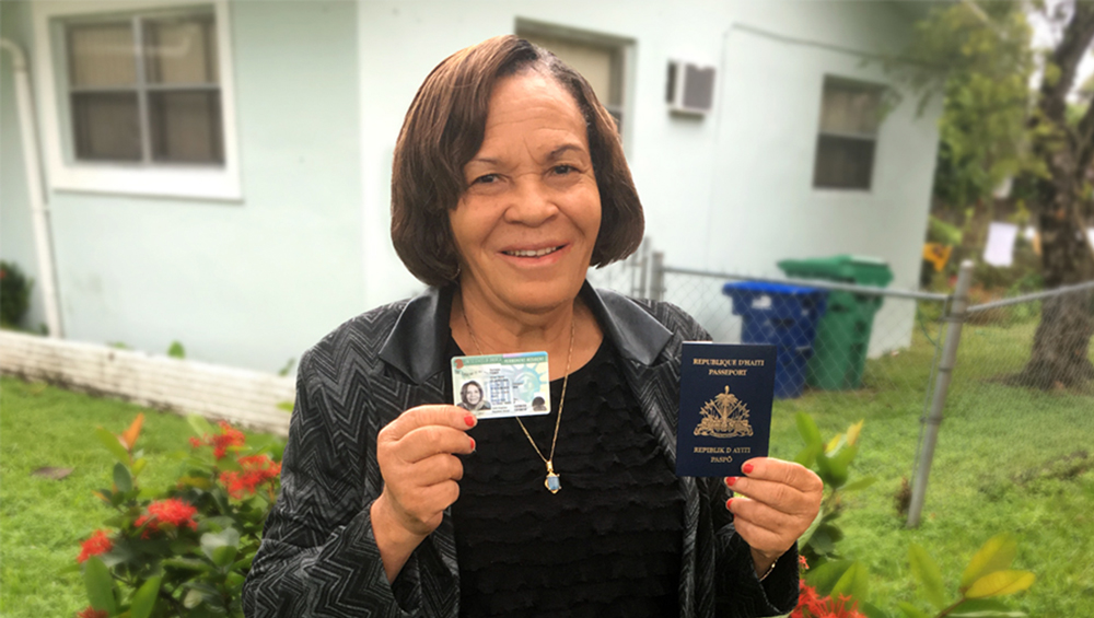 Haitian mother holding green card and passport.