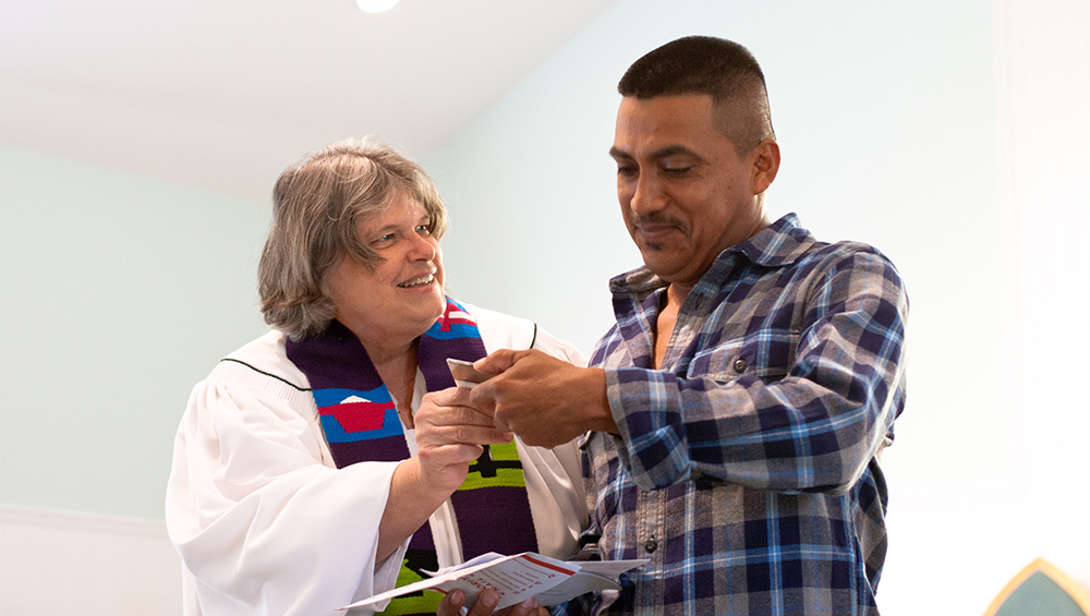 Janet presenting a client with his green card at a church service in Redland, Florida.